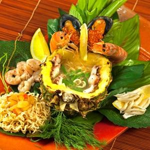 Θαλασσινά και λαχανικά με noodles σερβιρισμένα σε φωλιά από ανανά